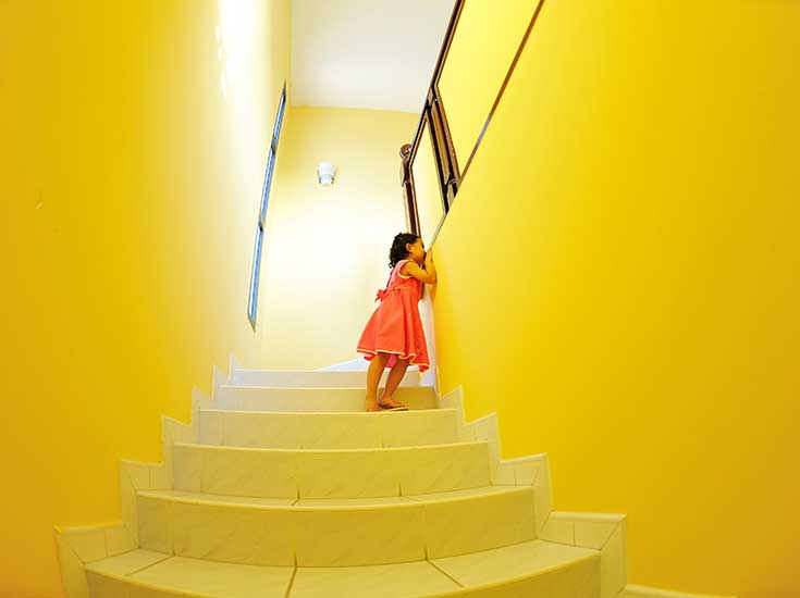 Coatings image of girl in bright yellow decorated room