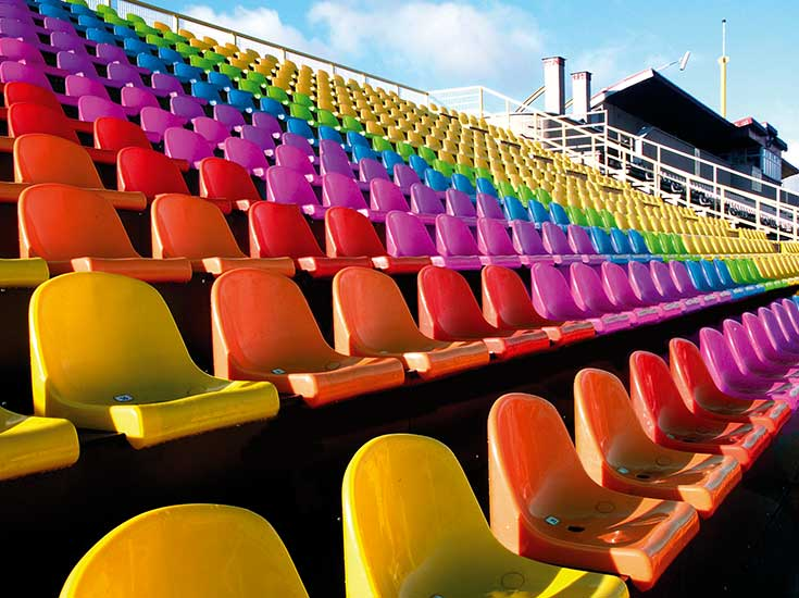 Multi-coloured plastic chairs in stadium